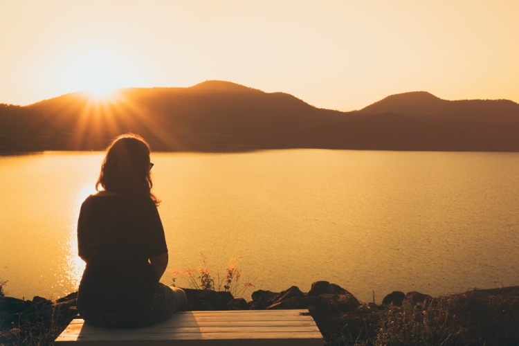 Woman sitting on pier overlooking lake at sunset